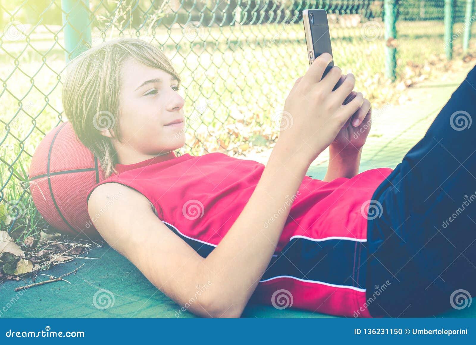 Smartphone van het tienergebruik met vrienden voor spelbasketbal openlucht - het gezonde sportieve concept van de tienerslevensst
