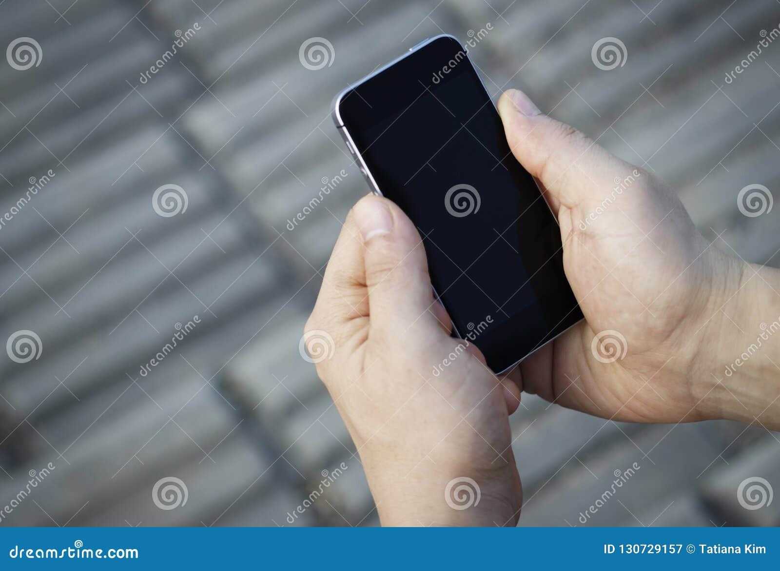 Smartphone w męskich rękach, odgórny widok, outdoors