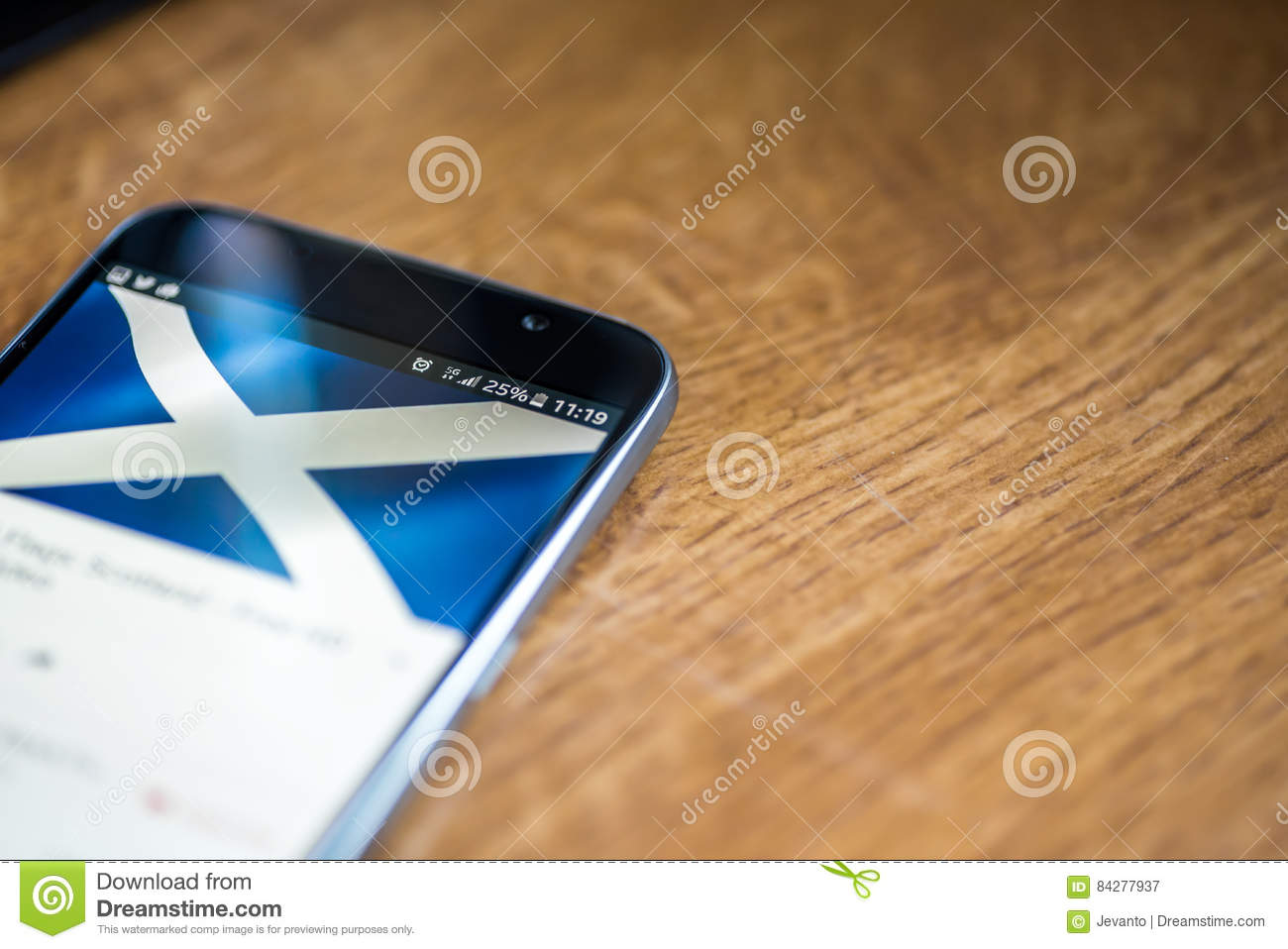 Smartphone on wooden background with 5G network sign 25 per cent charge and Scotland flag on the screen