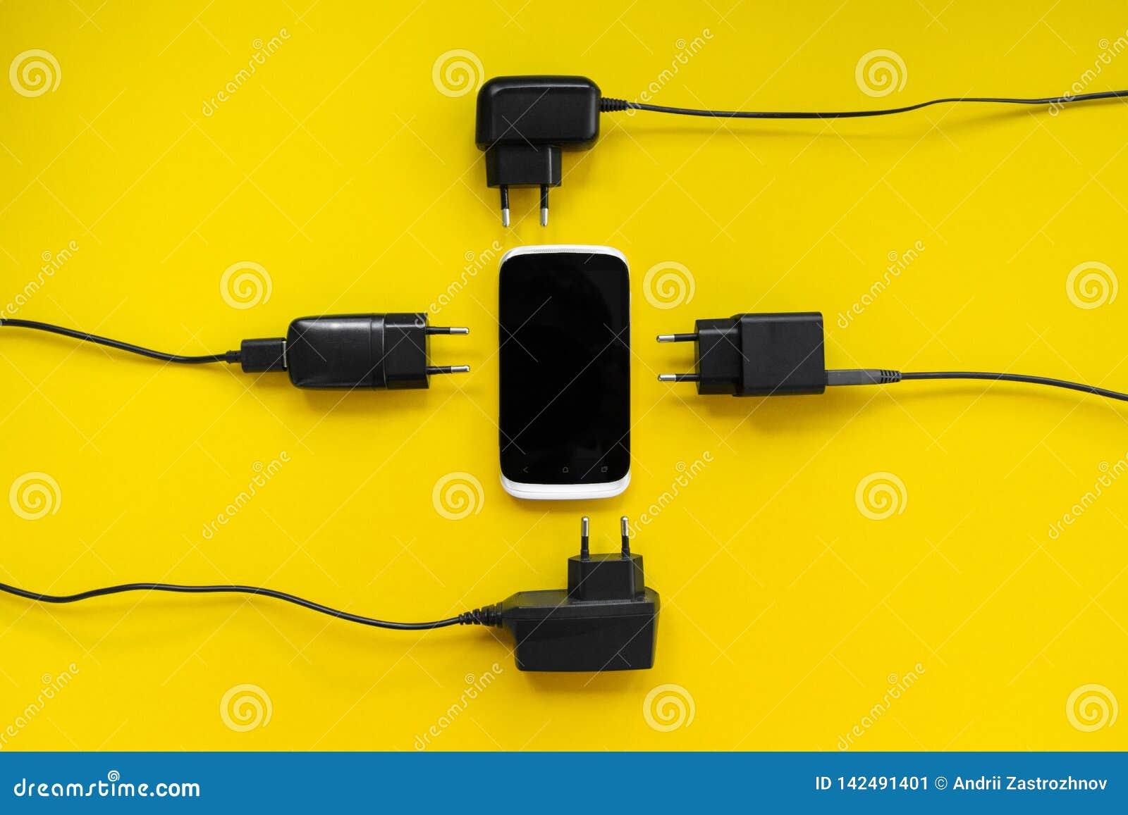 Smartphone y cargadores alrededor en un fondo amarillo, concepto