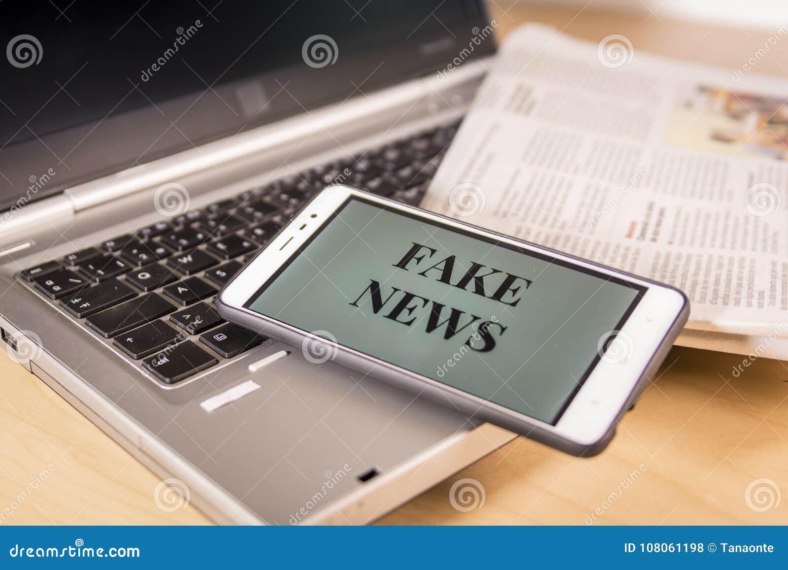 Smartphone z Sfałszowanymi wiadomości słowami na ekranie nad gazetą i laptopem Sfałszowana wiadomość, bajerowania pojęcie