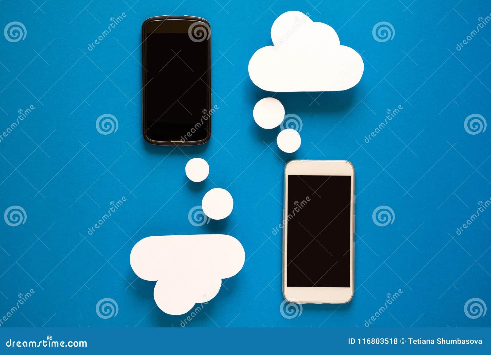 Smartphones con i fumetti di carta su fondo blu Concetto di comunicazione
