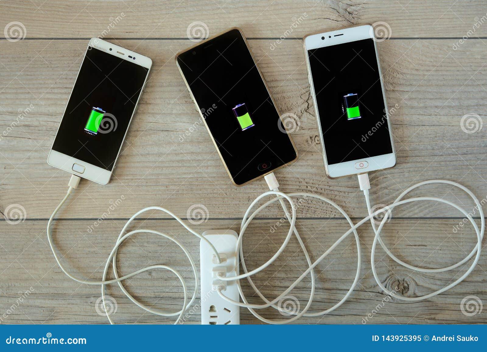 Smartphones wordt geladen van de lader en ligt zij aan zij