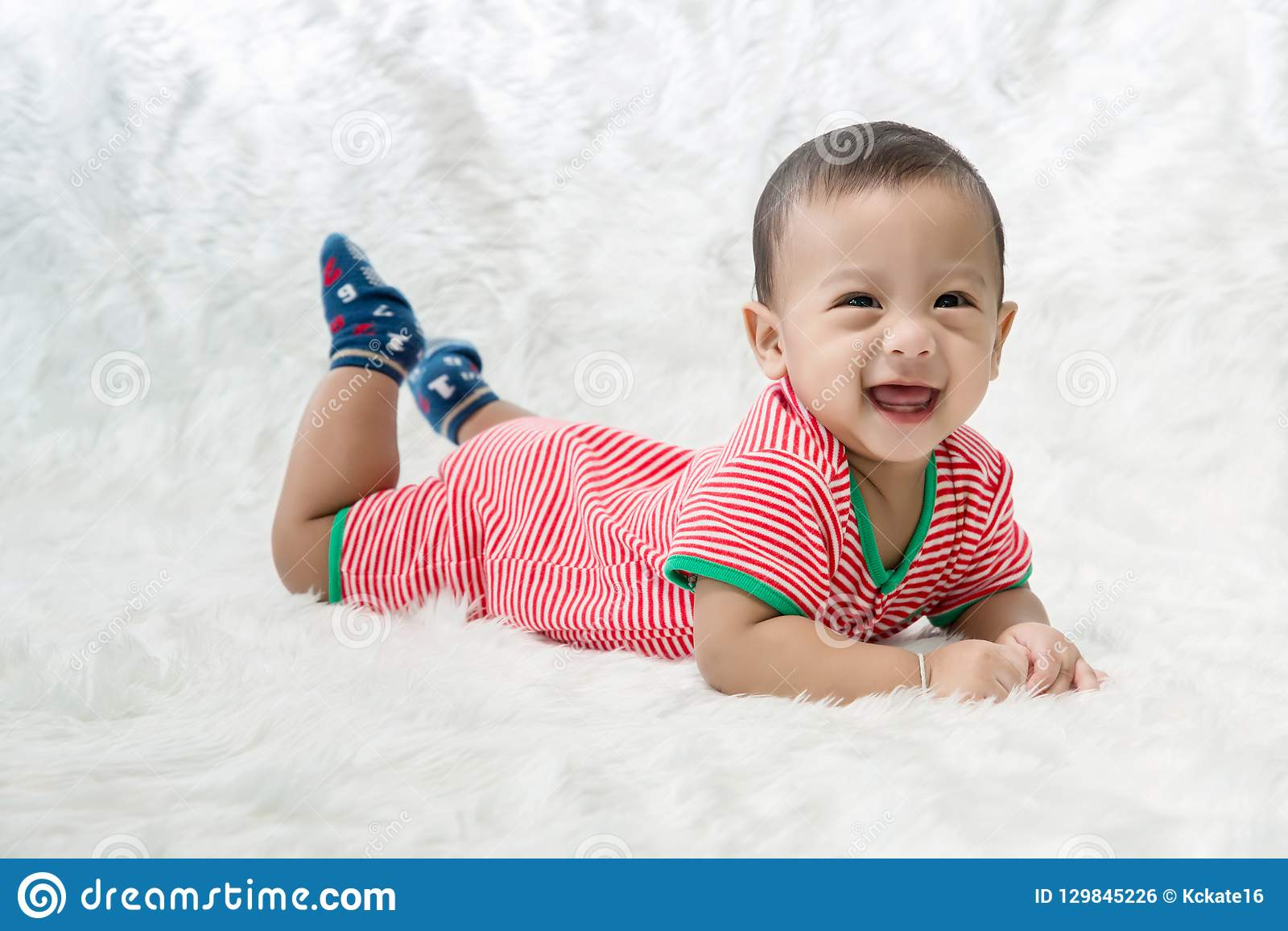 Smile baby boy is shooting in the studio. fashion image of baby and family. Lovely baby lie down on a soft white carpet.