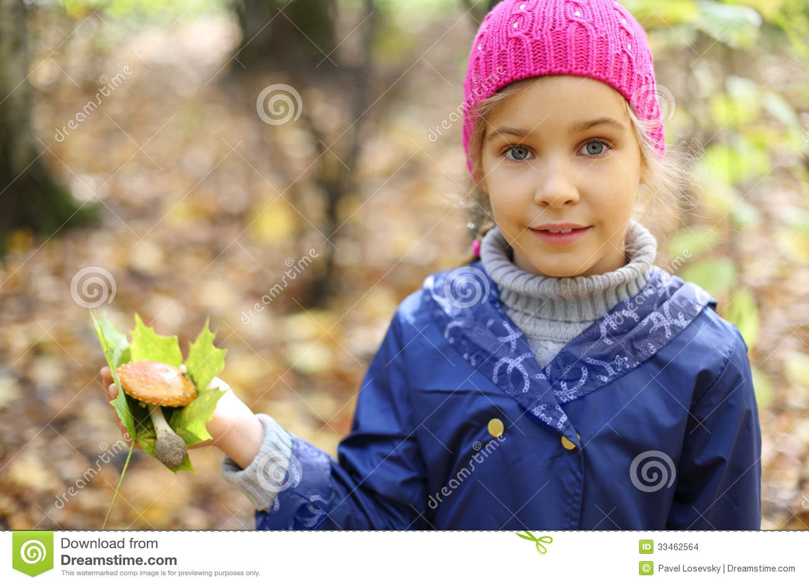 Smile little girl holds maple leaf