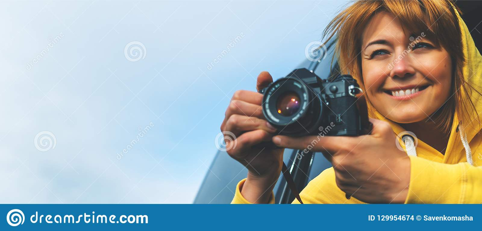 Smile tourist girl in an open window of a auto car taking photography click on retro vintage photo camera, photographer looking