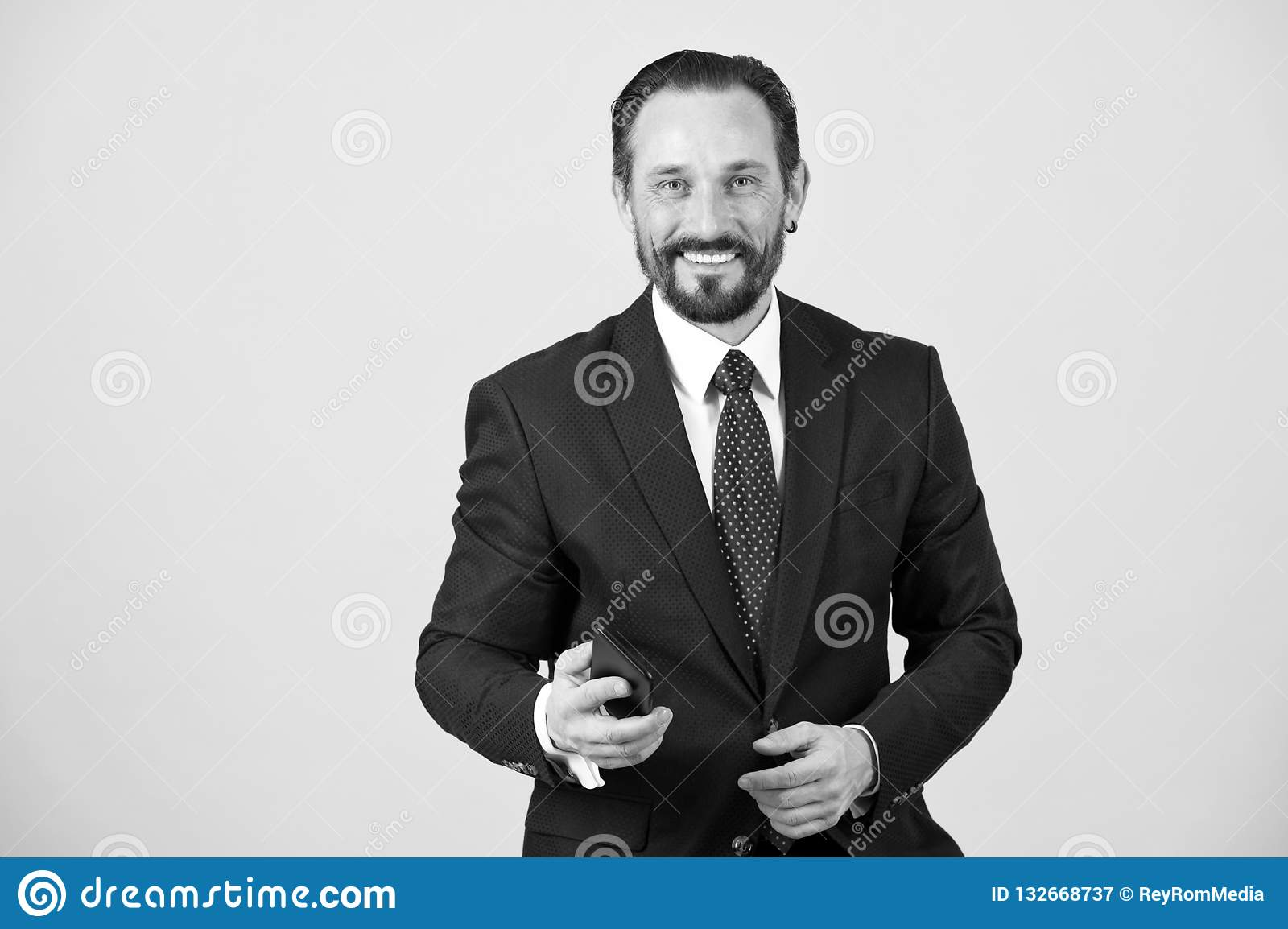 Smiled and happy businessman in suit and tie hold smartphone