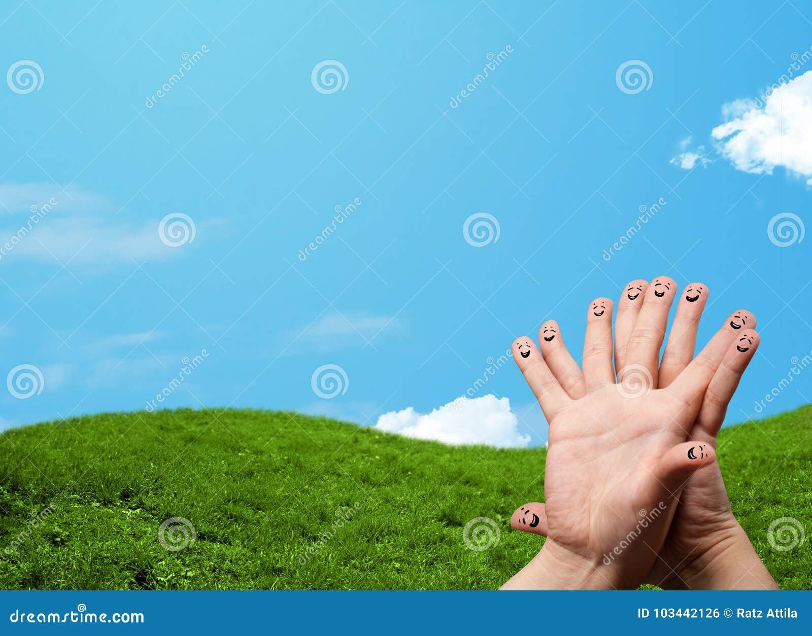 Smiley alegres do dedo com cenário da paisagem no fundo