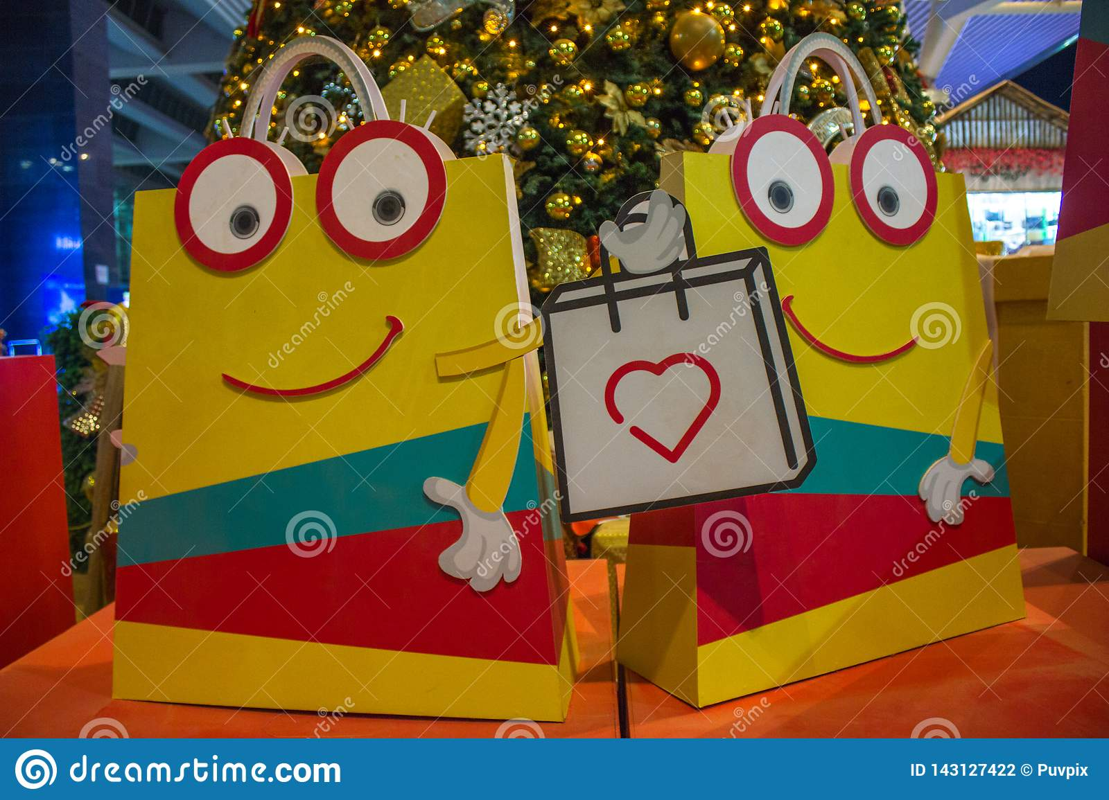 Smiley animated shopping bags with christmas tree in the background.