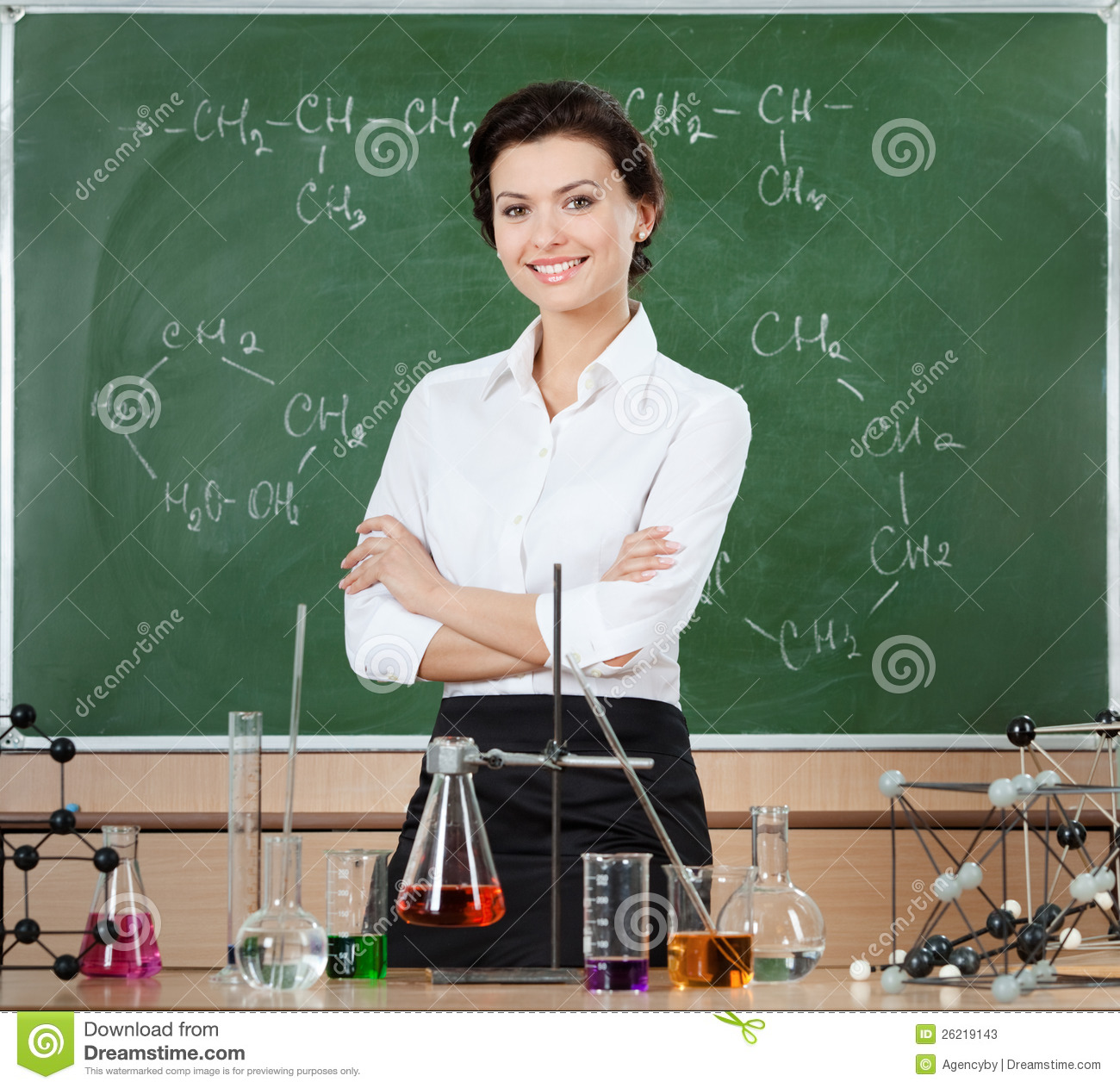 Smiley chemistry teacher surrounded with chemical glassware stands ...