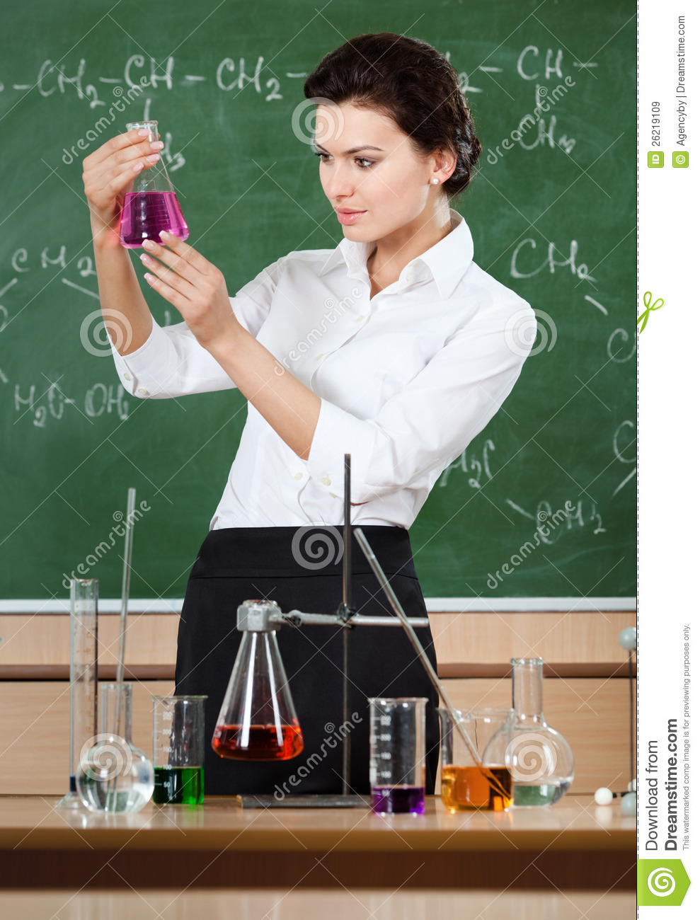 smiley chemistry teacher examines conical flask royalty