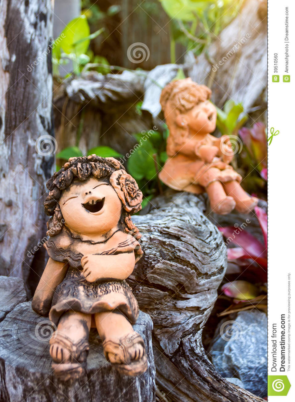 Smiley clay doll on wood in the park.