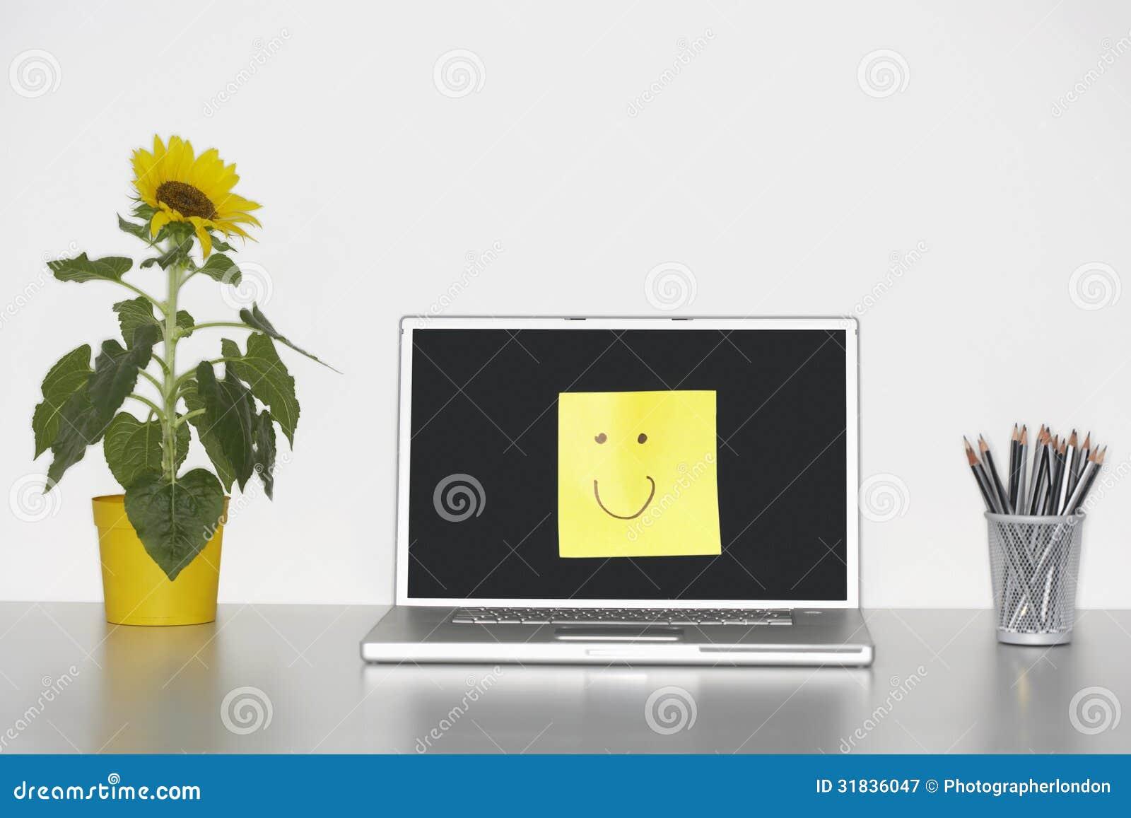 Smiley Face On Laptop Screen met bloemen en Potloden