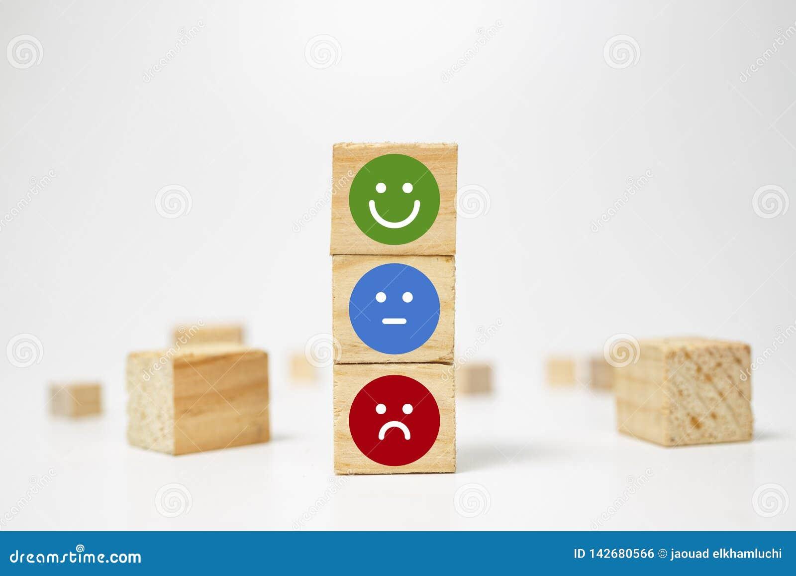 Smiley framsida på träsnittkuben - affärsservice som klassar kunderfarenhet, tillfredsställelsegranskningsbegrepp - återkoppling