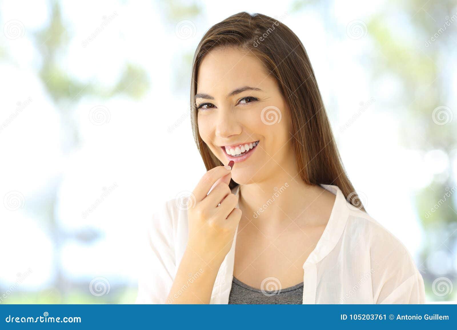 Smiley kobieta bierze pigułkę patrzeje ciebie