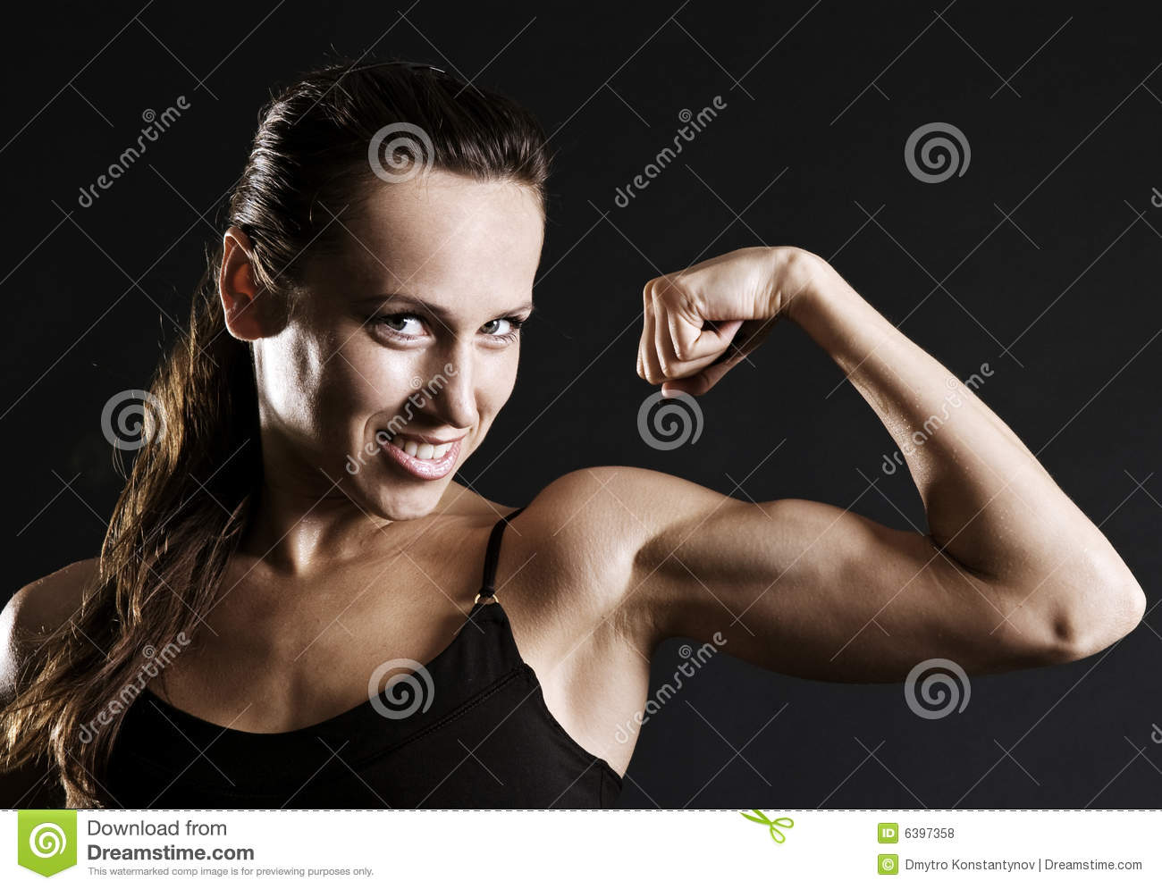 Smiley sportswoman showing her muscles