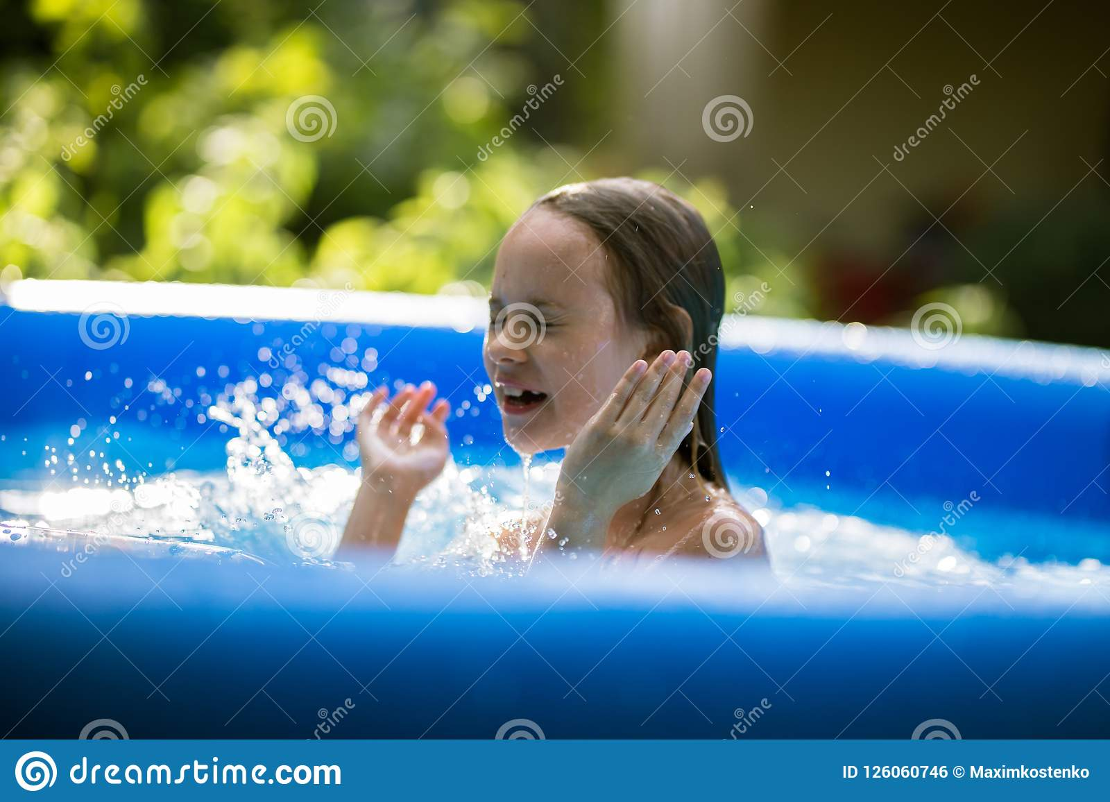 Smiling adorable seven years old girl playing and having fun in inflatable pool