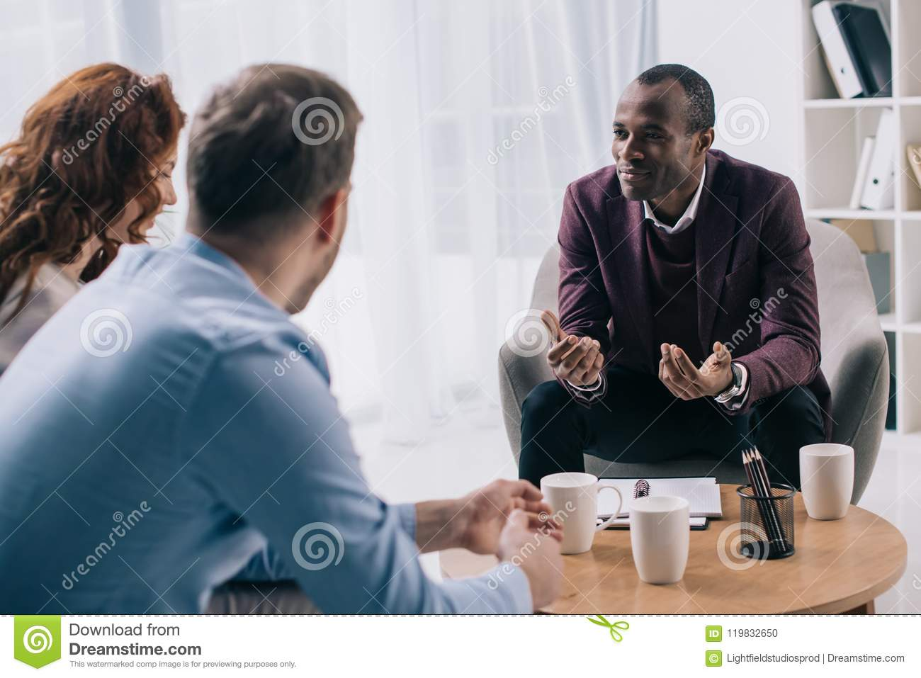 Smiling african american counselor talking to young couple