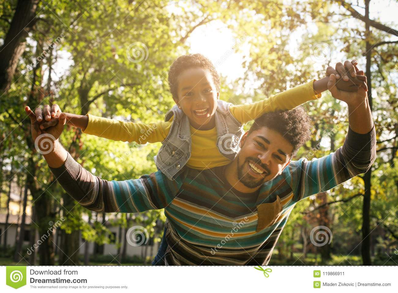 Smiling African American father carrying his daughter on piggyback and holding hands.