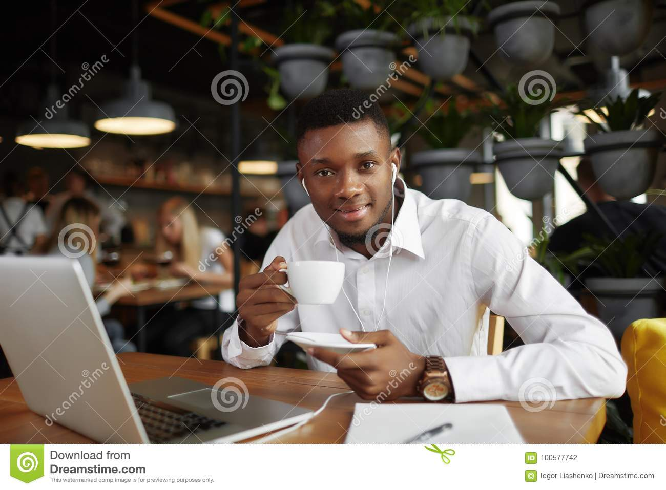 Smiling african man at coffee break in cafe.