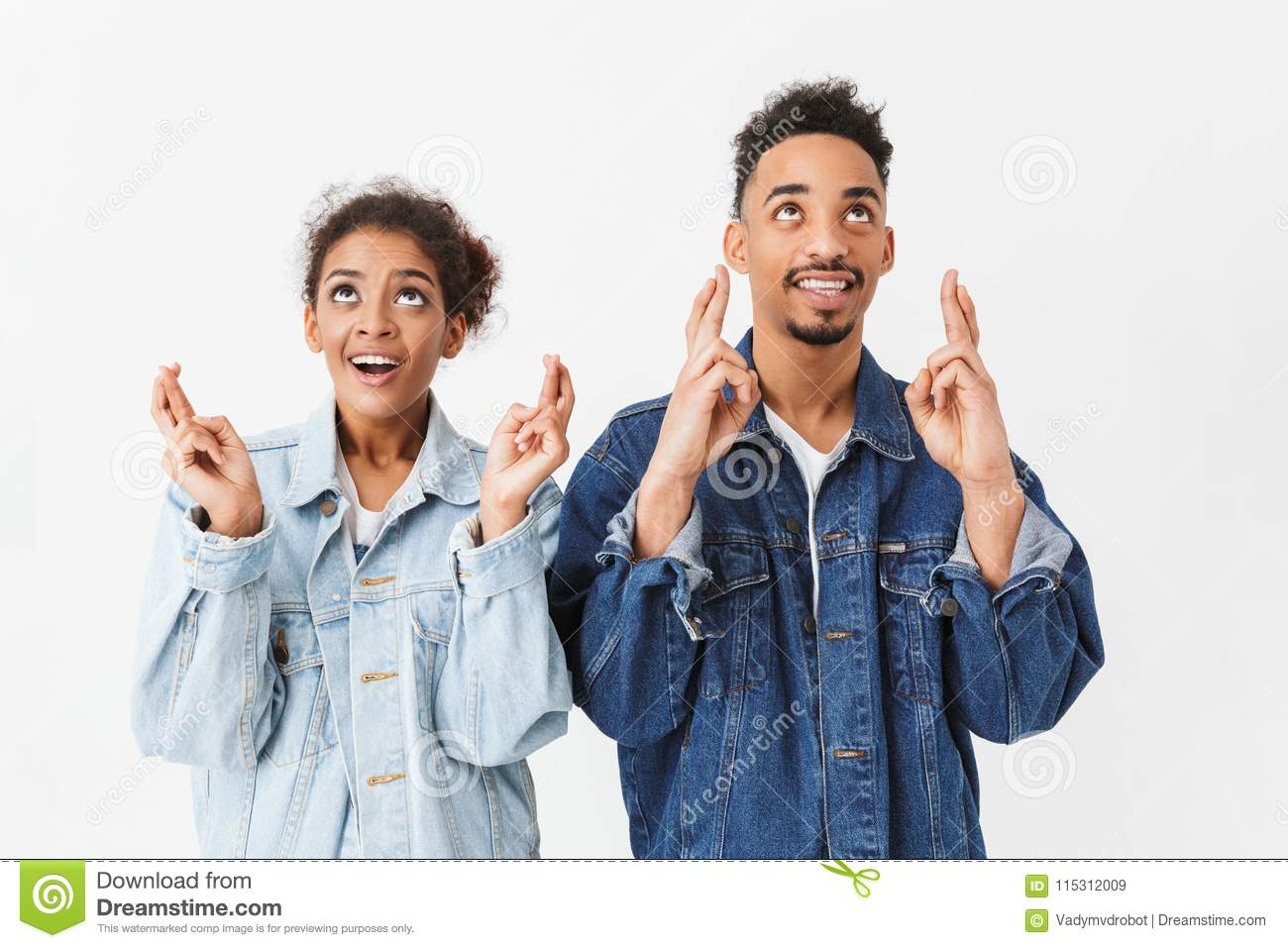 Smiling african couple in denim shirts praying together