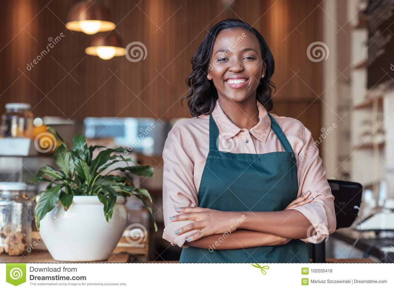 Smiling African entrepreneur standing at the counter of her cafe