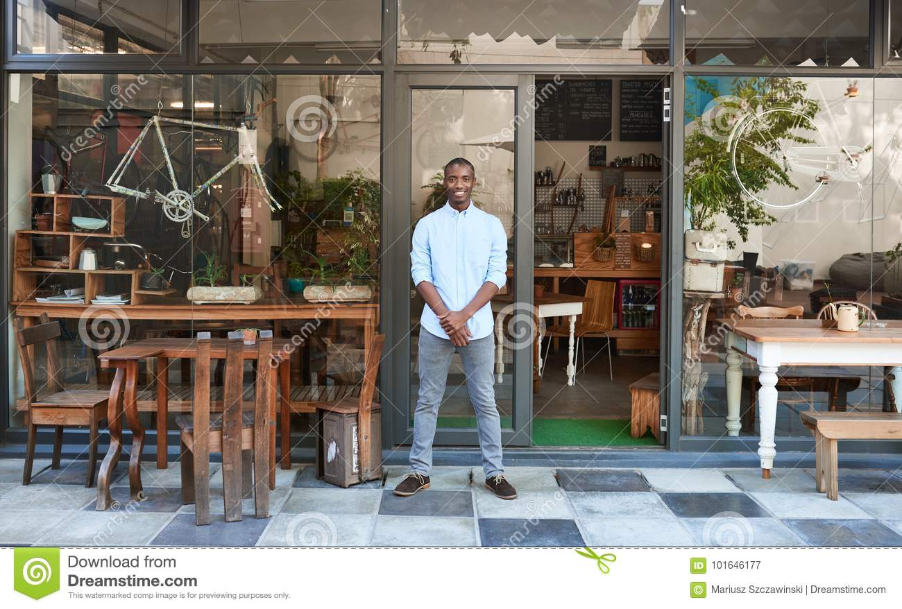 Smiling African entrepreneur standing welcomingly in front of his cafe