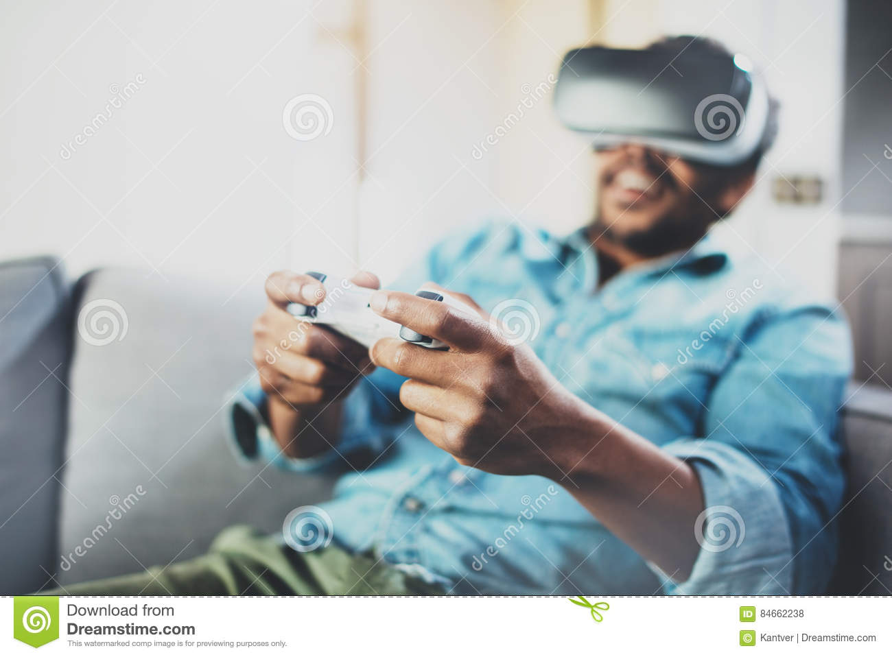 d04b3b94315 Smiling african man enjoying virtual reality glasses while sitting on sofa.Young  guy with vr headset or 3d spectacles and controller gamepad playing video  ...