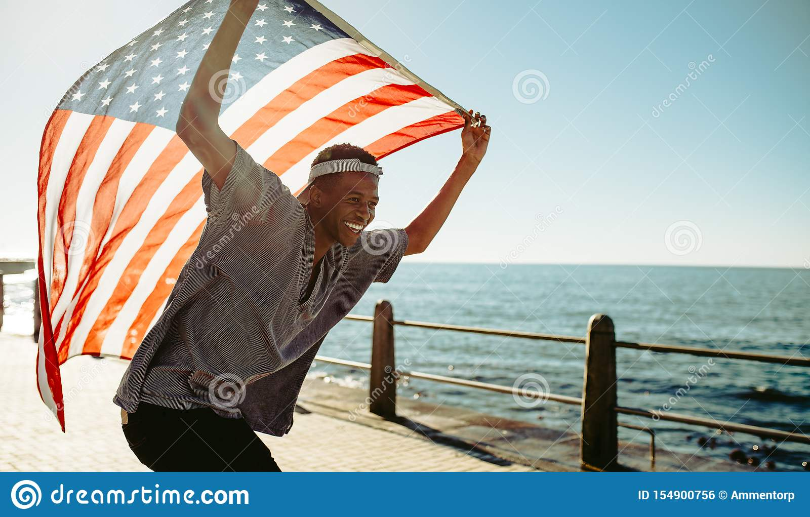 Cheerful young guy at promenade with american flag