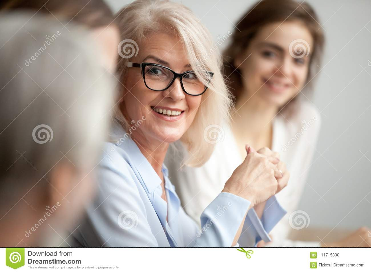 Smiling aged businesswoman looking listening to colleague at tea
