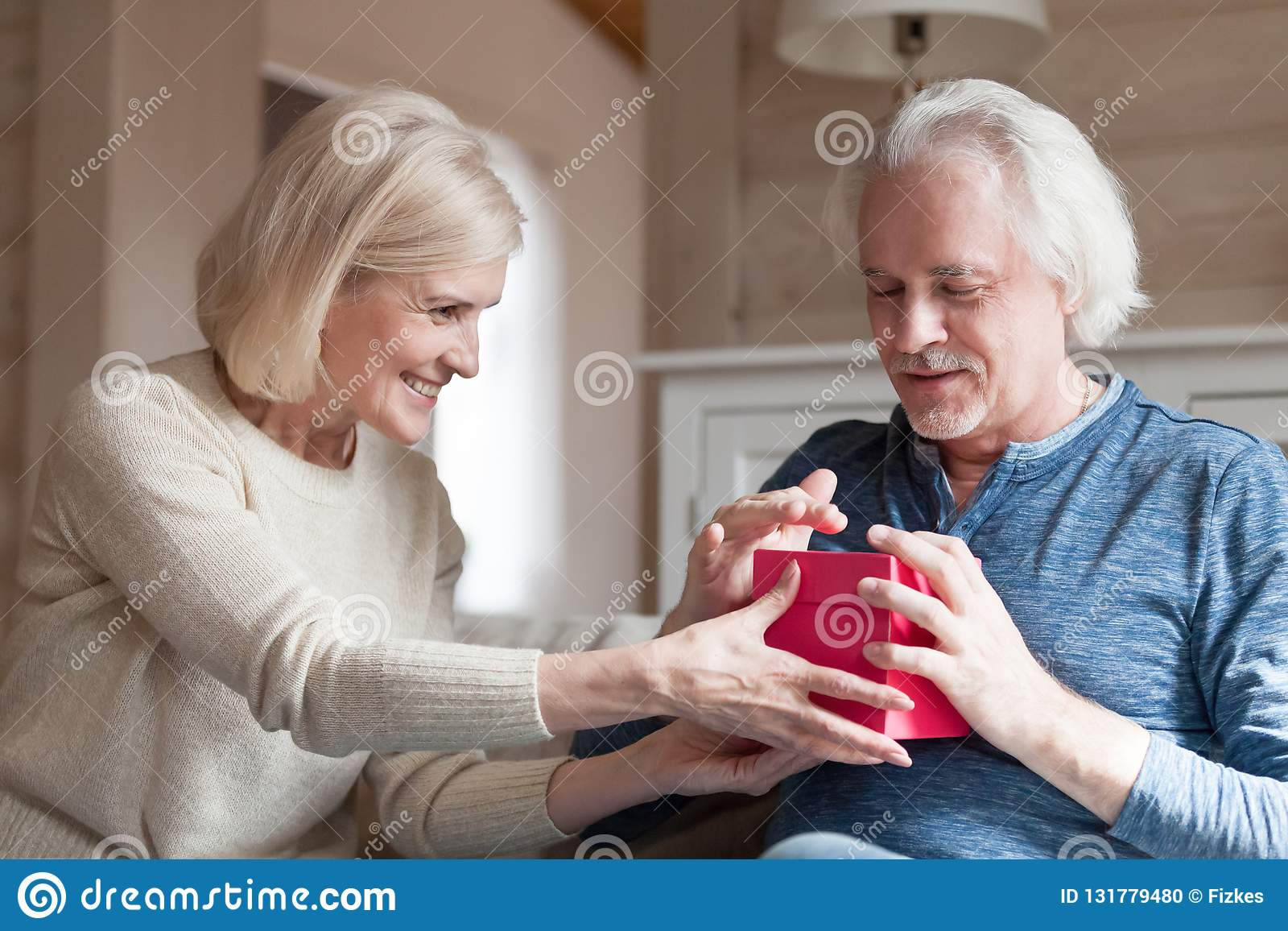 Smiling Aged Wife Making Surprise Presenting Gift To
