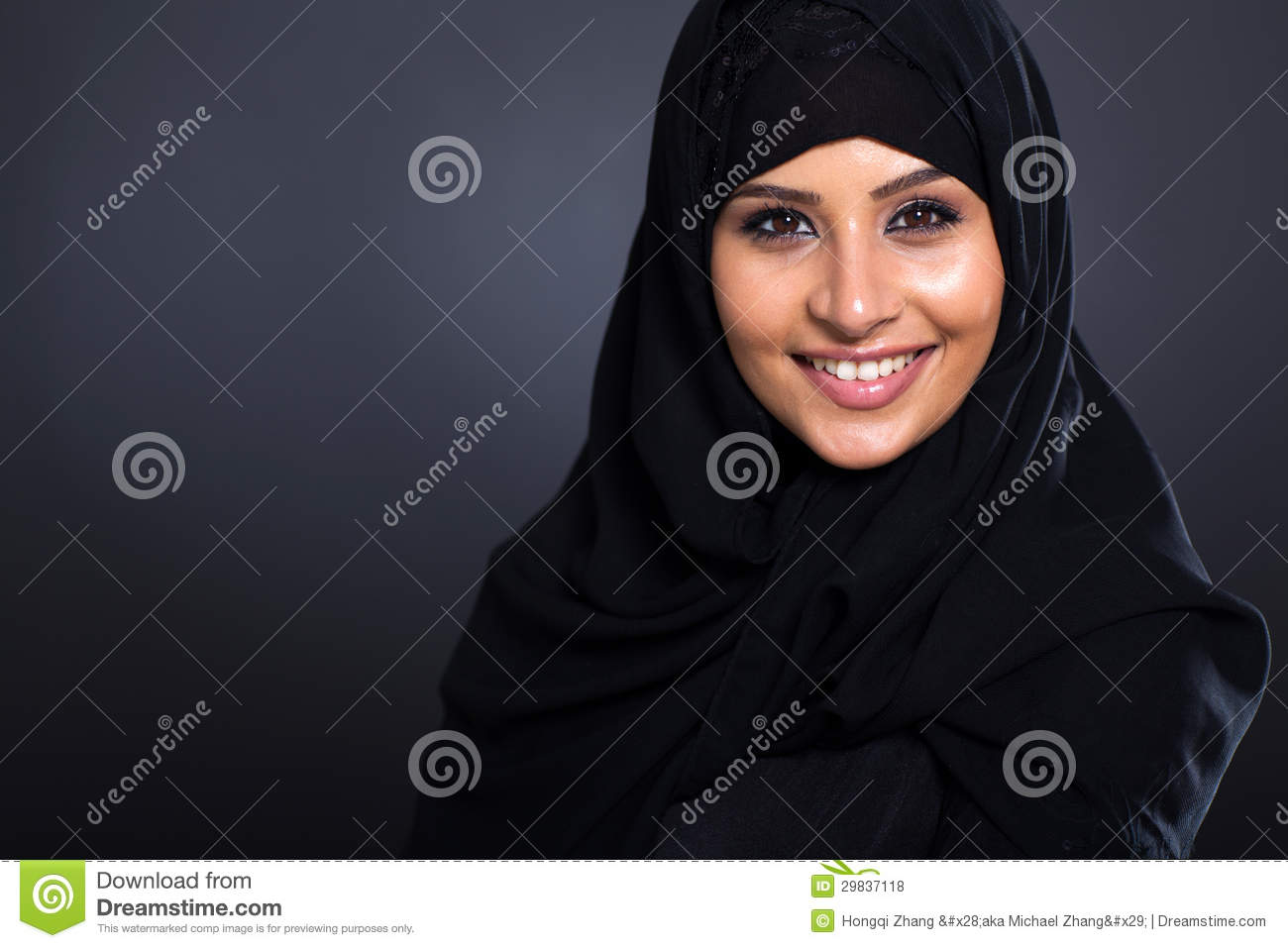 Smiling Arabic woman in traditional clothing on black background