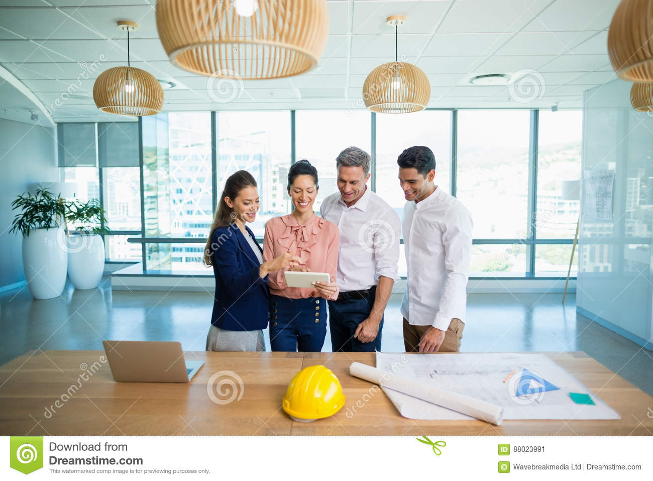 Smiling architects discussing over digital tablet
