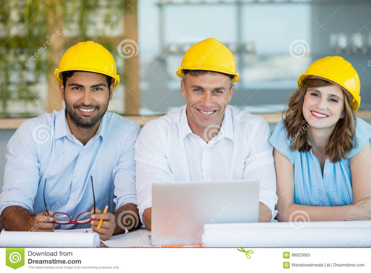 Smiling architects sitting together in conference room