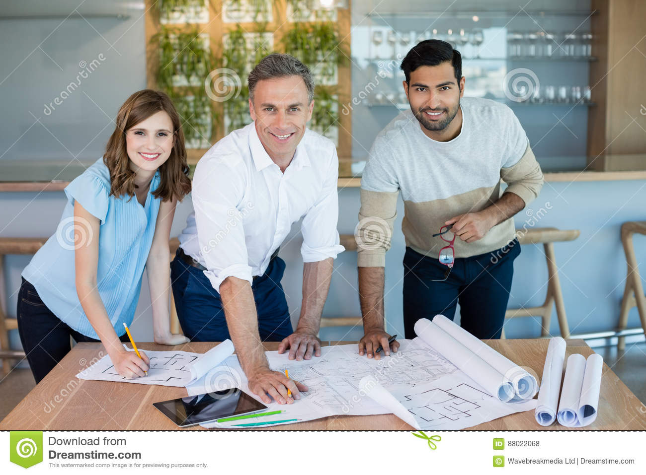 Smiling architects working over blueprint in conference room