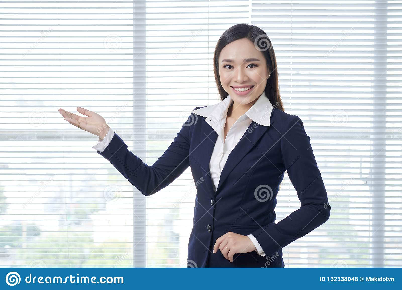 Smiling asian businesswoman standing in bright office