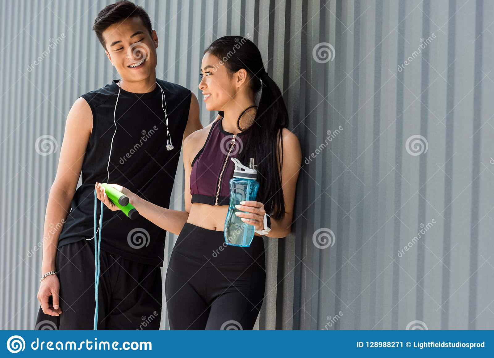 smiling asian sportswoman holding bottle of water and giving jump rope to young sportsman