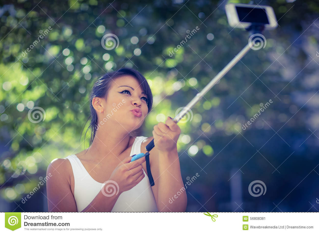Smiling athletic woman taking selfies with selfiestick