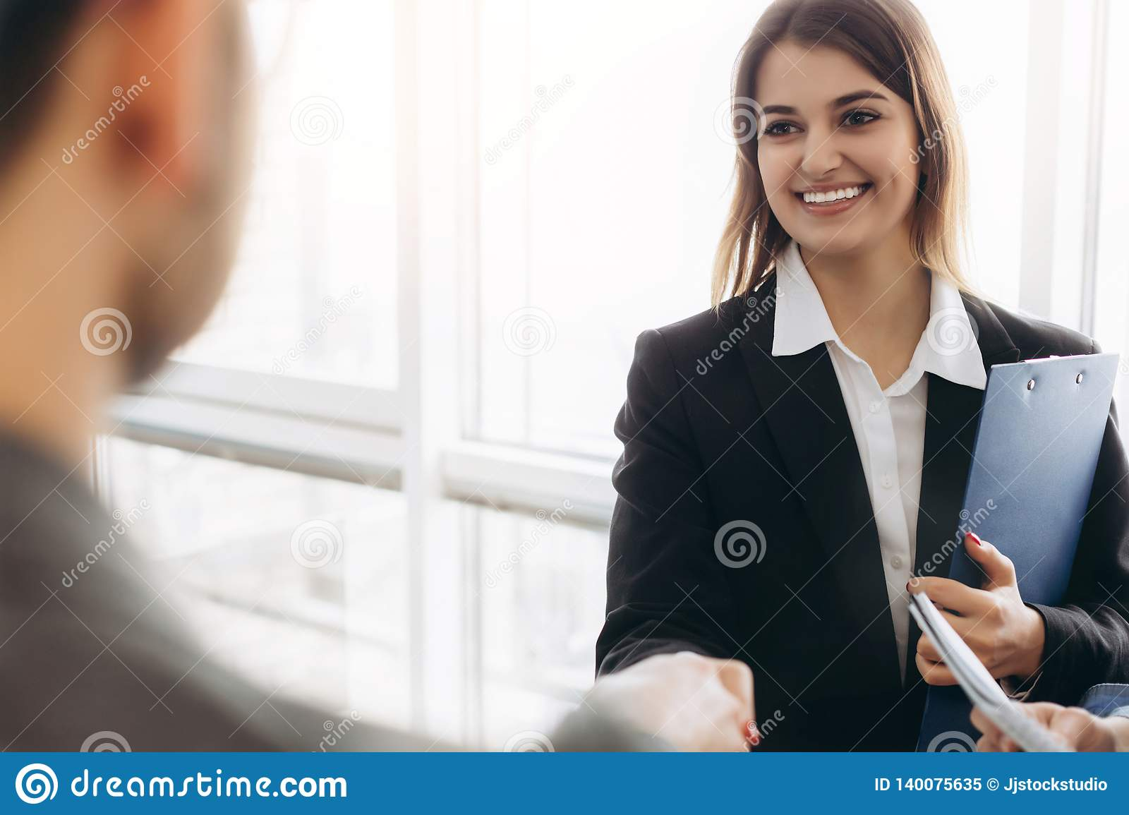 Smiling attractive businesswoman handshaking with businessman after pleasant talk, good relationships. Business concept photo