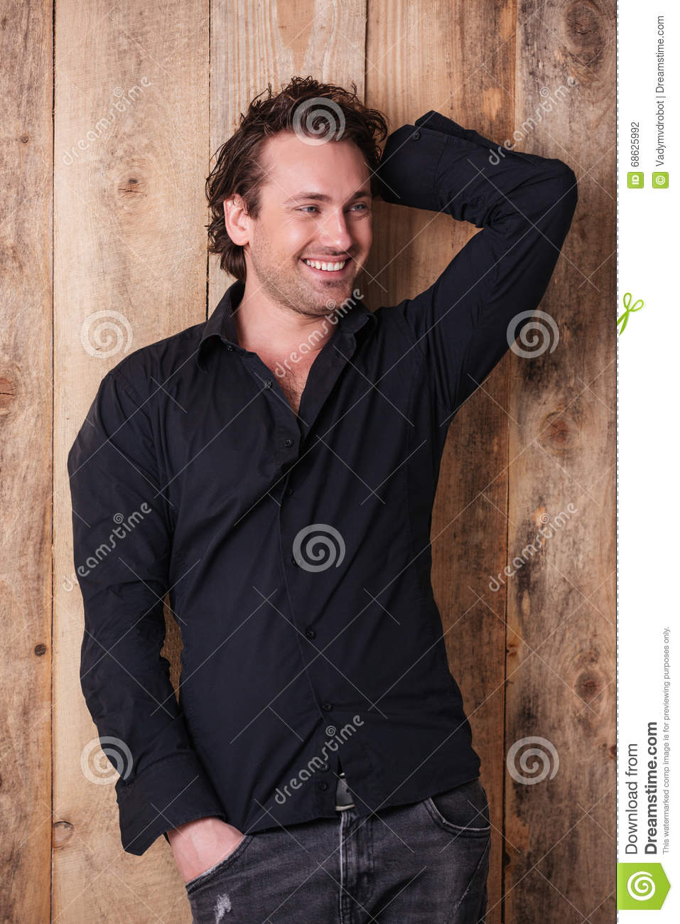 9d4494905660 Smiling Attractive Young Man In Black Shirt Standing And Posing ...