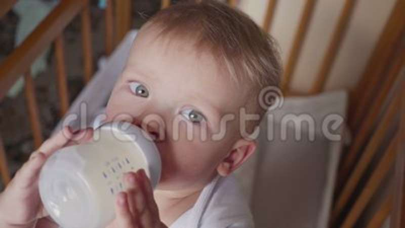 smiling baby boy standing and drinking milk from a bottle stock