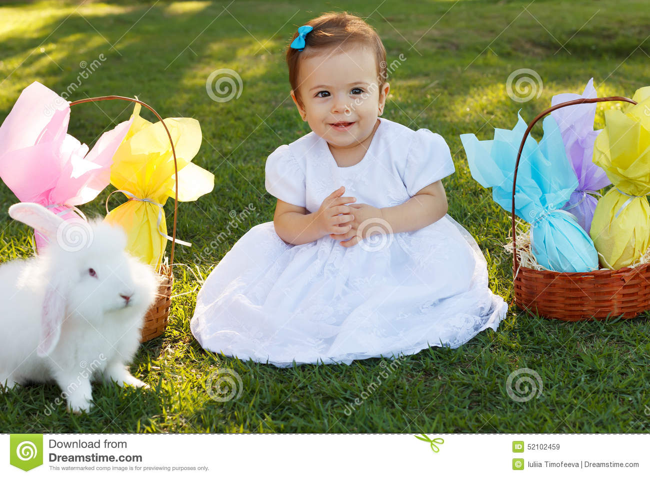 87082a9a2f2e Cute smiling baby girl in white dress with wicker basket with chocolate  eggs and white rabbit for Easter holiday in park on green grass.