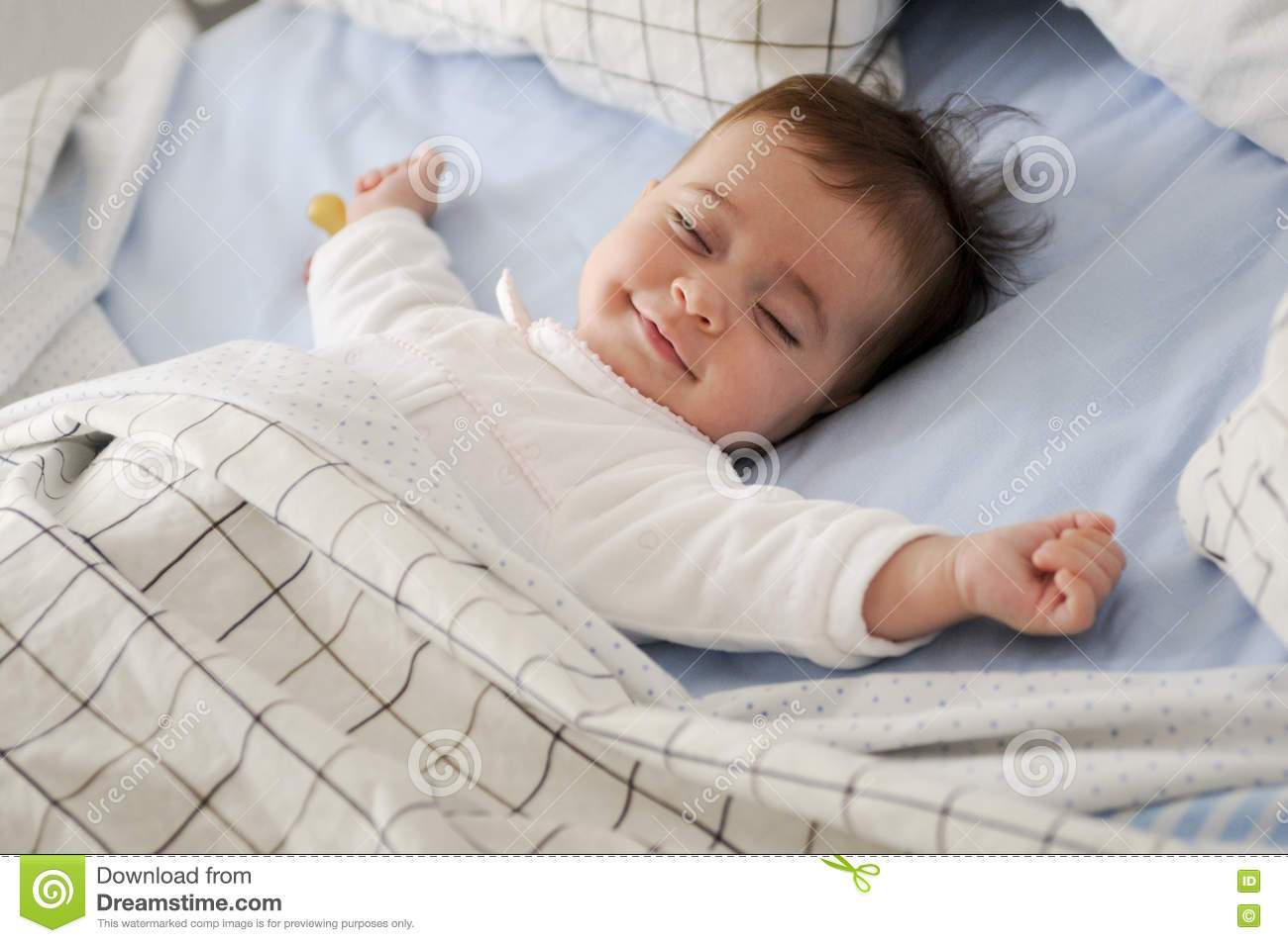 Smiling baby girl lying on a bed sleeping