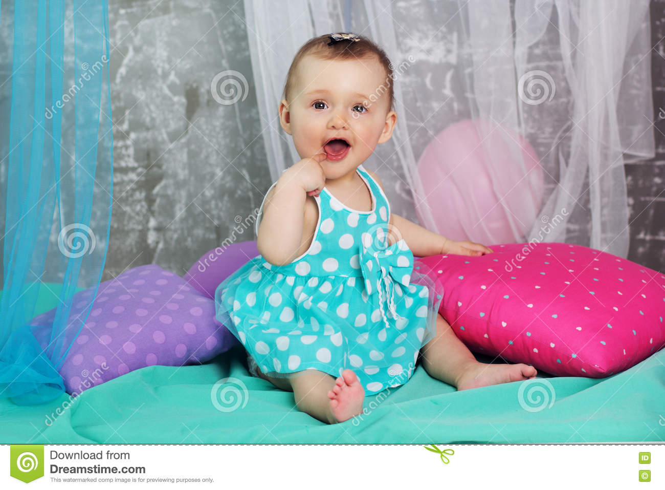 d3cedb752 Happy cute baby girl is wearing nice dress sitting with colorful pillows