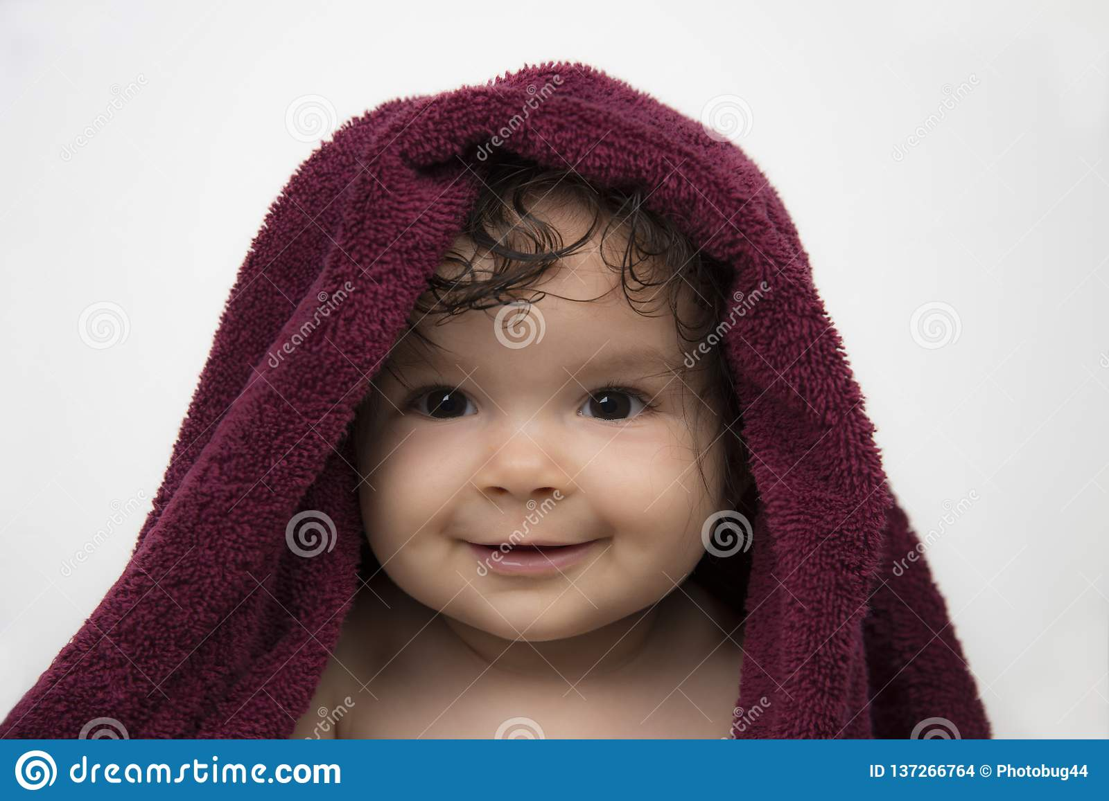Smiling baby in red bath towel