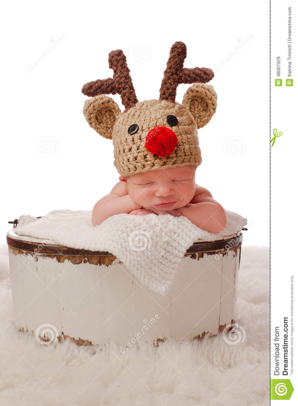 d27838e13 A smiling eight day old newborn baby boy wearing a red nosed reindeer hat  and sitting in an antique wooden bucket. Photographed in a studio on a  white ...