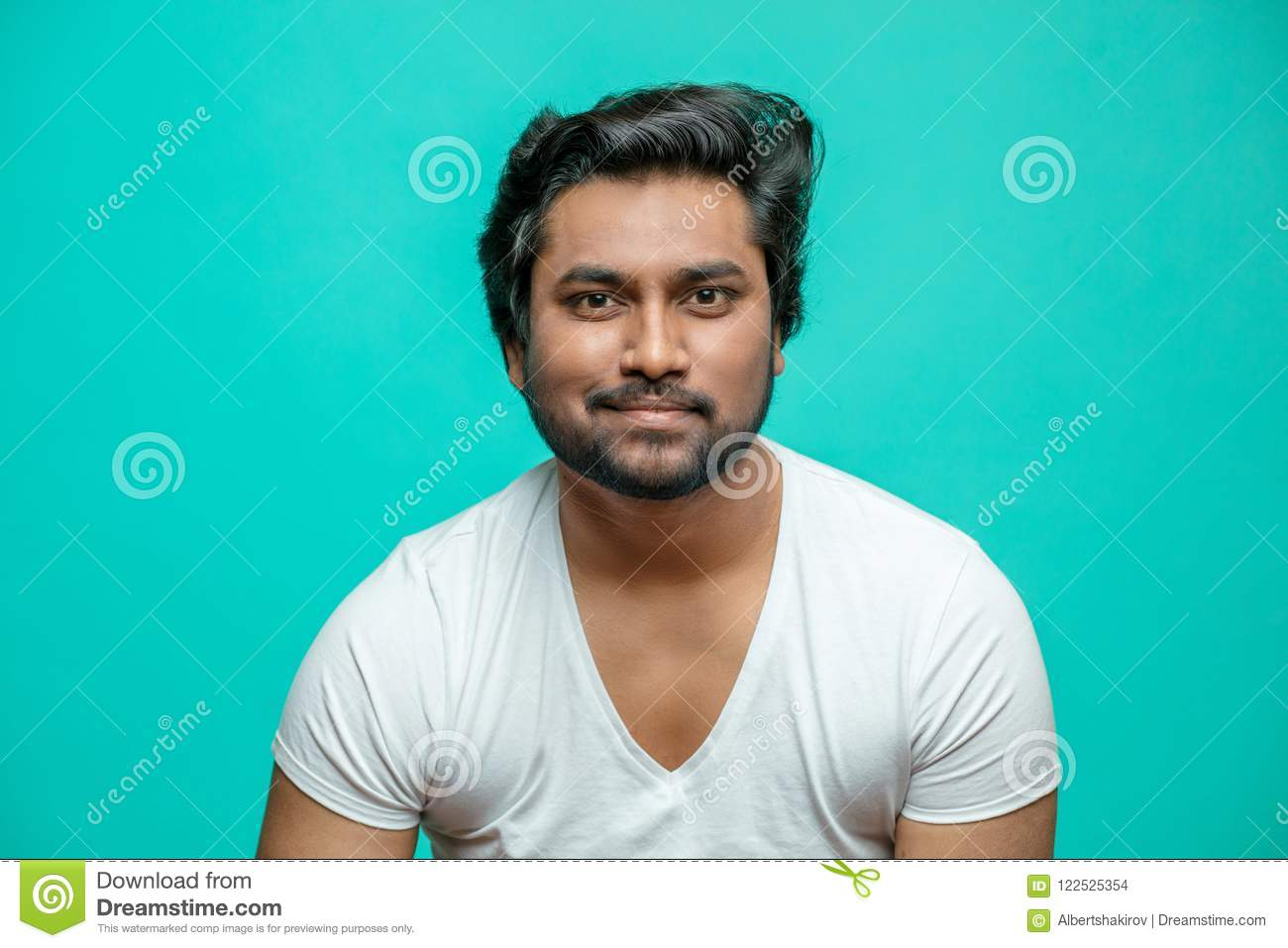 Smiling bearded brutal Indian guy looking at the camera
