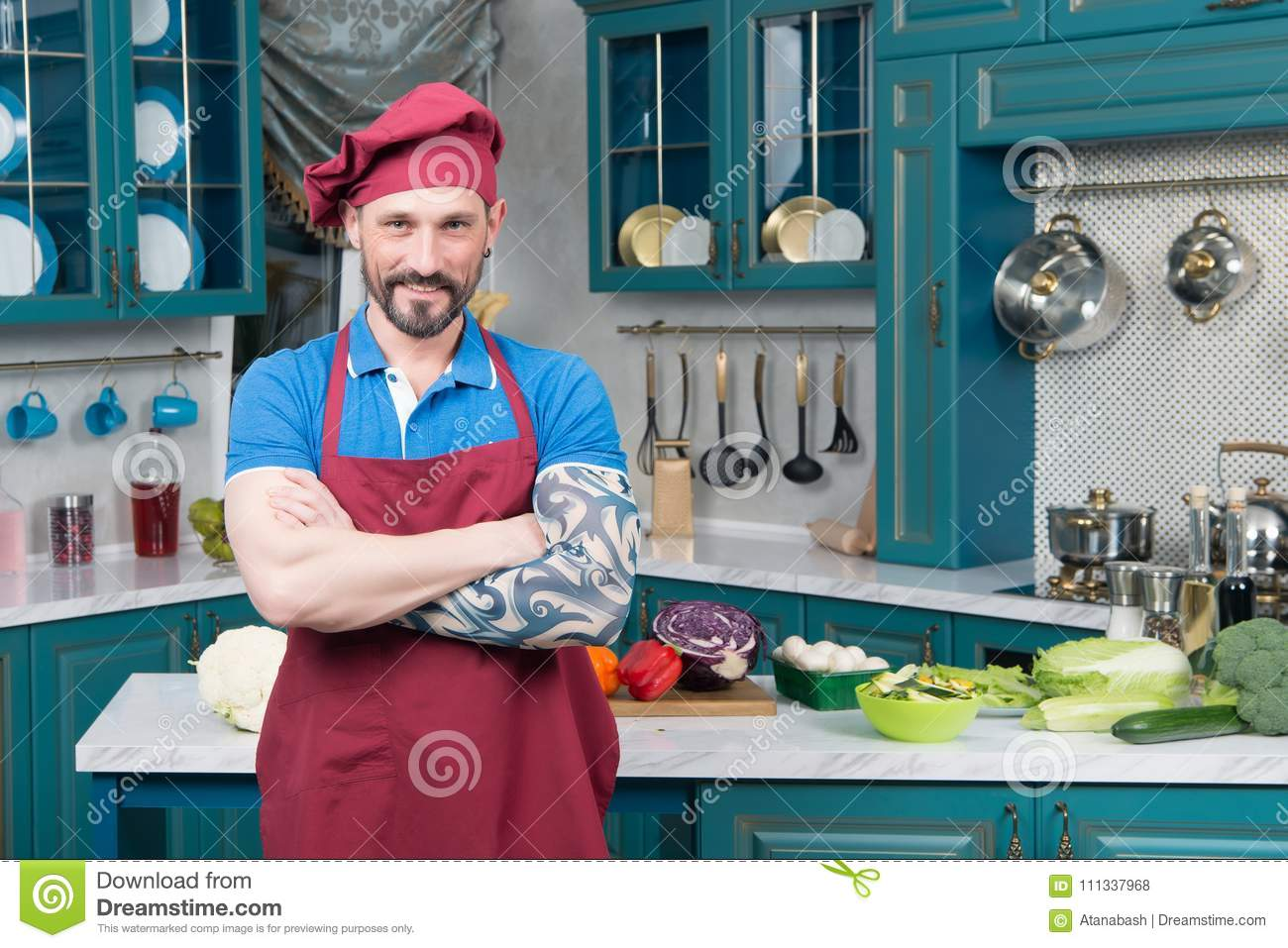Smiling Bearded Chef With Tattooed Hand In Red Apron And Red Hat On ...