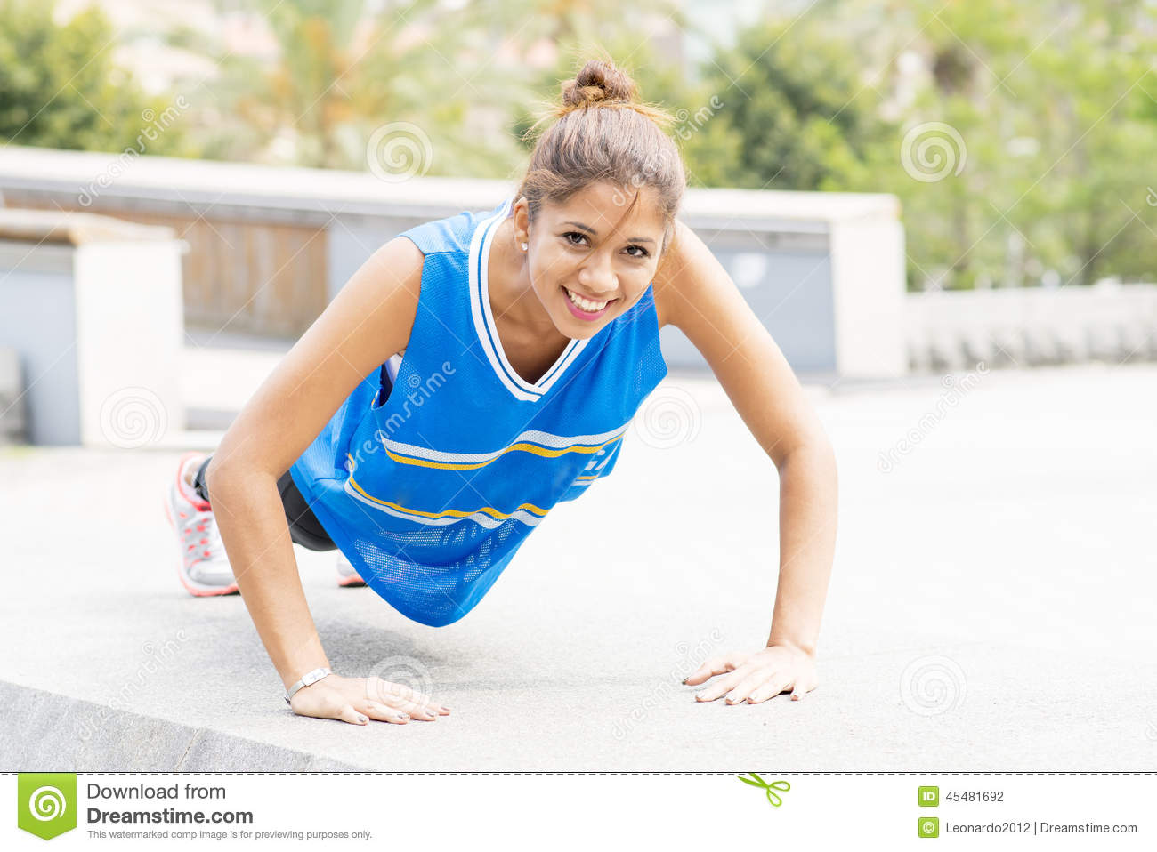 Smiling beautiful athletic woman doing pushups in the street.