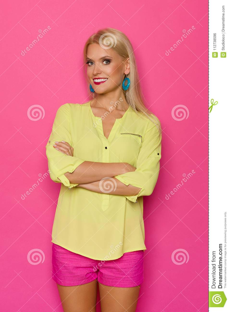 eea34b84aca44 Smiling beautiful blond woman in yellow shirt and pink shorts is holding  arms crossed and looking at camera. Three quarter length studio shot on pink  ...